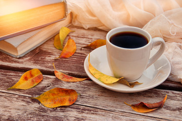 image of coffee cup over wooden table and autumn leaves