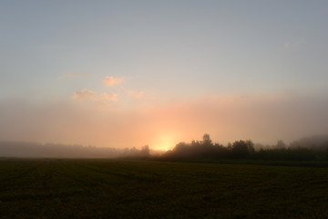 Sunrise over the foggy early morning field in the countryside
