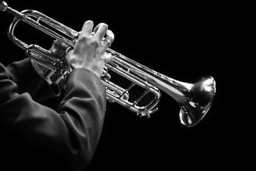 Keuken foto achterwand Muziek Hands of a musician playing on a trumpet closeup in black and white tones on a black background