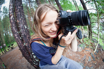Young woman taking photos in autumn forest with camera