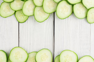 Many scattered slices fresh green cucumbers on old white wooden planks