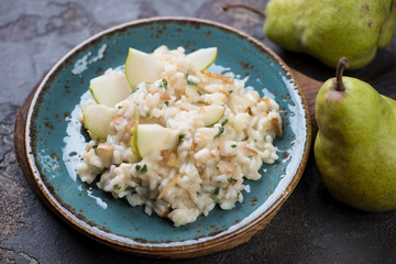 Risotto with pears on a turquoise plate, selective focus, studio shot