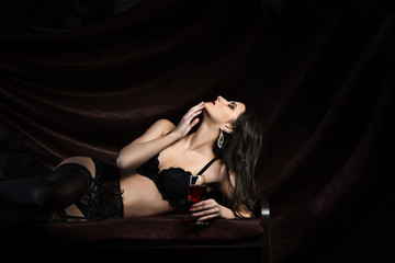 Beautiful woman in black lace lingerie lays on the sofa with glass of red wine