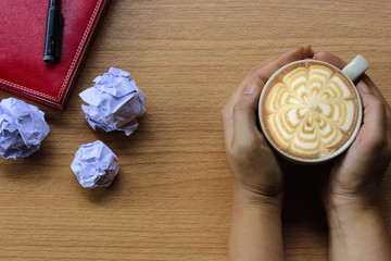 Hands holding cup coffee with crumpled paper and red book etc.Concept stress