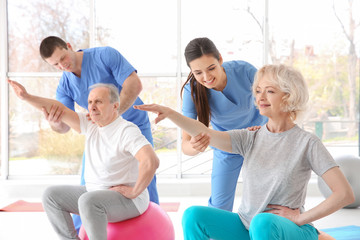 Physiotherapists working with elderly patients in modern clinic