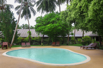 Bungalow with swimming pool at resort in summer day