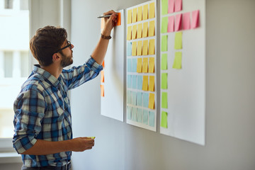Young creative man writing down ideas on wall full of sticky notes