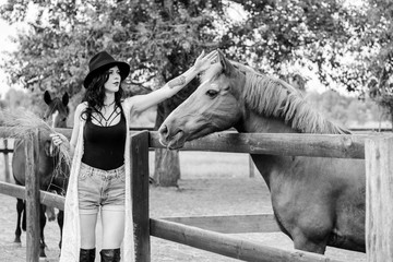 Sweet pretty woman on a rancho near beautiful horses farm posing at camera and have fun, curly brunette girl in american country style