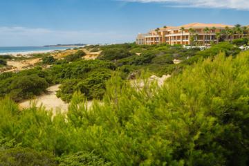 Sand dunes between hotels and beach of La Barrosa in Sancti Petri, Cadiz, Spain