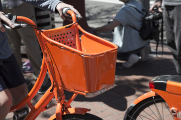 Hands Wrapped Around Handlebars of Vibrant Orange Bike with Basket, Non-Descript People in Background, Shallow Field of Depth - Portland, Oregon