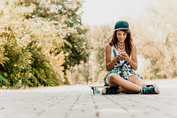 Hipster girl sitting on skateboard and using smart phone