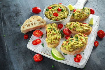 Homemade Guacamole toast with chili pepper, parsley on white wooden board