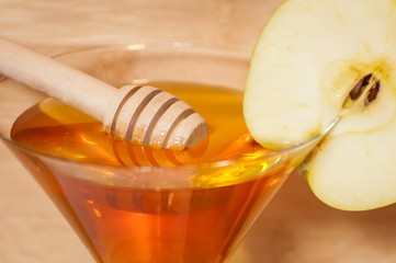 Honey stick in the pure honey inside of a martini glass decorated with an apple slice. Rosh Hashanah (Jewish New Year) greeting card illustration. Shana tova, have a sweet New Year greeting card.
