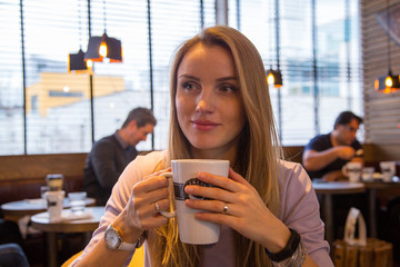 Beautiful girl drinking coffee at the cosy cafe in Malmo near Western Harbour district