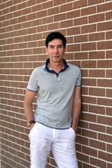 Счастливый улыбающийся уверенный в себе молодой человек в рубашку и белые летние брюки позирует возле кирпичной стены