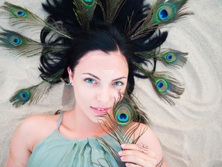 Outdoor fashion portrait of beautiful brunette lady at beach with flash tattoos lying with peacock feathers in hair. Gypsy boho style, Woman in green dress.