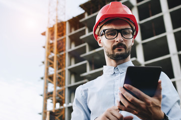 Security inspector with tablet in hand on onstruction site. Businessman builder looks into industrial tablet. Concept of engineering and industry