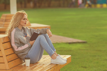 Trendy woman in sitting on the bench in city park. Drinking takeaway coffee and writing or drawing something in notebook.