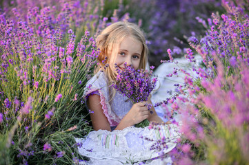 Beautiful girl in a field of lavender on sunset. Beautiful girl in amazing dress walk on the field...