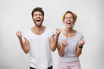 People, happiness, winning, victory, success and good luck. Indoor shot of two young Caucasian people man and woman expressing their excitement and delight by shouting Yes and clenching fists