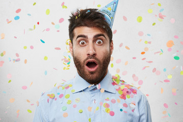 Young Caucasian man dressed in formal shirt and having party cap on head, celebrating his birtday, looking with bugged eyes and widely opened mouth into camera being surprised to recieve many presents
