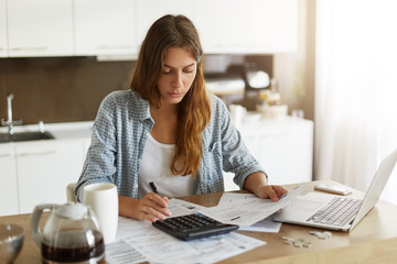 Picture of young Caucasian woman wearing casual clothes at home, full of sad and restless thoughts, feeling stressed calculating her debts for rent and making notes, surrounded with papers and gadgets