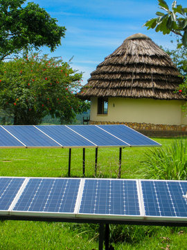Solar panels and a rural hut in Uganda countryside in Africa