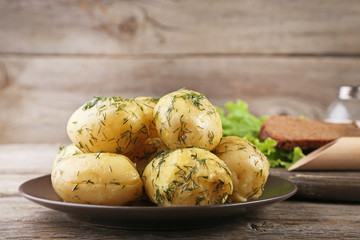Boiled potatoes with butter and dill in plate on wooden table