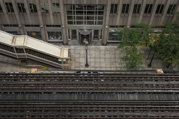 Looking down at elevated tracks and city sidewalk