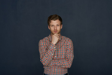 Human facial expressions and emotions. Waist-up shot of attractive guy with stubble standing at studio wall, holding hand on his chin, staring at camera with pensive thoughtul mysterious look