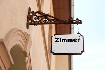 """Schild mit der Aufschrift """"Zimmer"""" an der Fassade eines Hauses"""