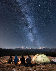 Rear view of four people sitting together beside camp and tent under beautiful night sky full of stars and milky way. On the background snow-covered mountains. Long exposure