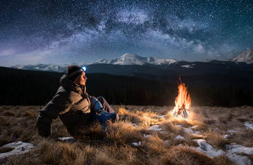 Male tourist have a rest in the mountains at night. Guy with a headlamp sitting near campfire under beautiful night sky full of stars and milky way, and enjoying night scene Wall mural
