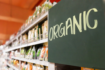 Organic food signage on modern supermarket grocery aisle