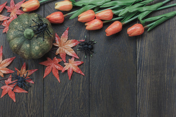 Table top of decoration sign Happy Halloween festival background. with beautiful orange tulip and maple leaf.Object on rustic wooden.Copy space for text information.Dark tone design.