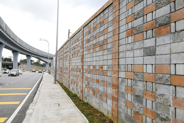 Concrete sound barrier wall next to busy highway rail track