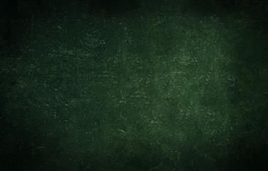 Dark green background of school blackboard colored vignetted texture. Dark green black shabby texture.