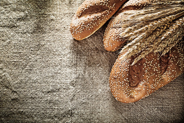 Crusty bread wheat ears on burlap background