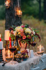 Wedding decor with  glasses, flowers, vases, candles and fruit on a ancient suitcase.