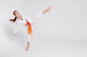 Karate girl in kimono in stand at studio background