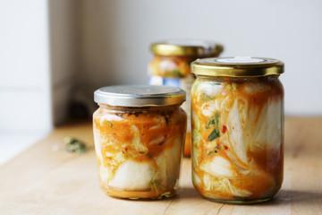 Homemade Kimchi in glass jar on kitchen board