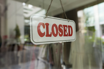 Close up shot of a close sign hanging up on the glass door.
