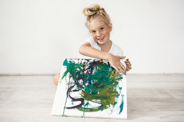 Close-up portrait of blond European little girl with hair bun and freckles smiling with all her teeth. Holding on her knees picture that she painted for her parents, feeling proud of herself. People