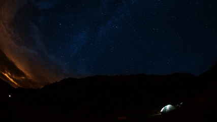 Night view of an illuminated camping tent located on the moor with starry night. Wide angle