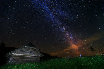 The Milky Way and old wooden hut, Transylvania, Romania, Europe