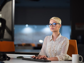 woman working on computer in dark office
