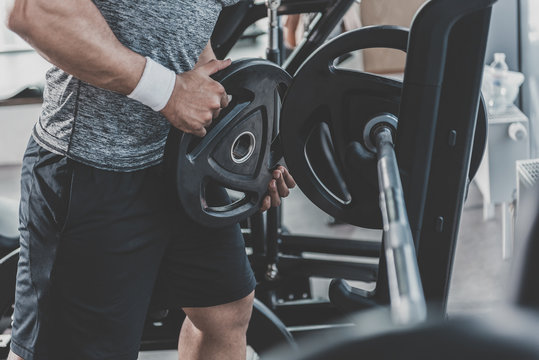 Man hands putting weight plate on barbell