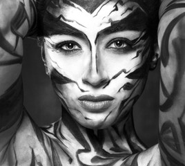 A beautiful woman with face art looks at us intently.