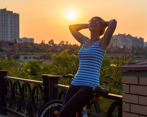 Woman stands and rests after a bike ride, holding her hands behind her head at sunset near the river
