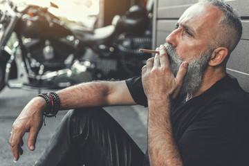Tired mature bearded man smoking